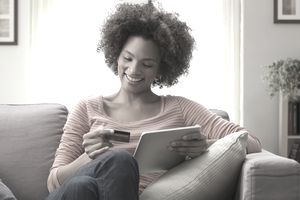 Woman uses credit card while holding a tablet.