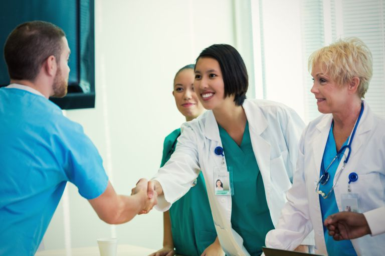 Doctors and nurses meet and shake hands