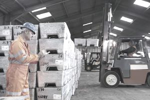 Worker inspecting metal alloy store in port