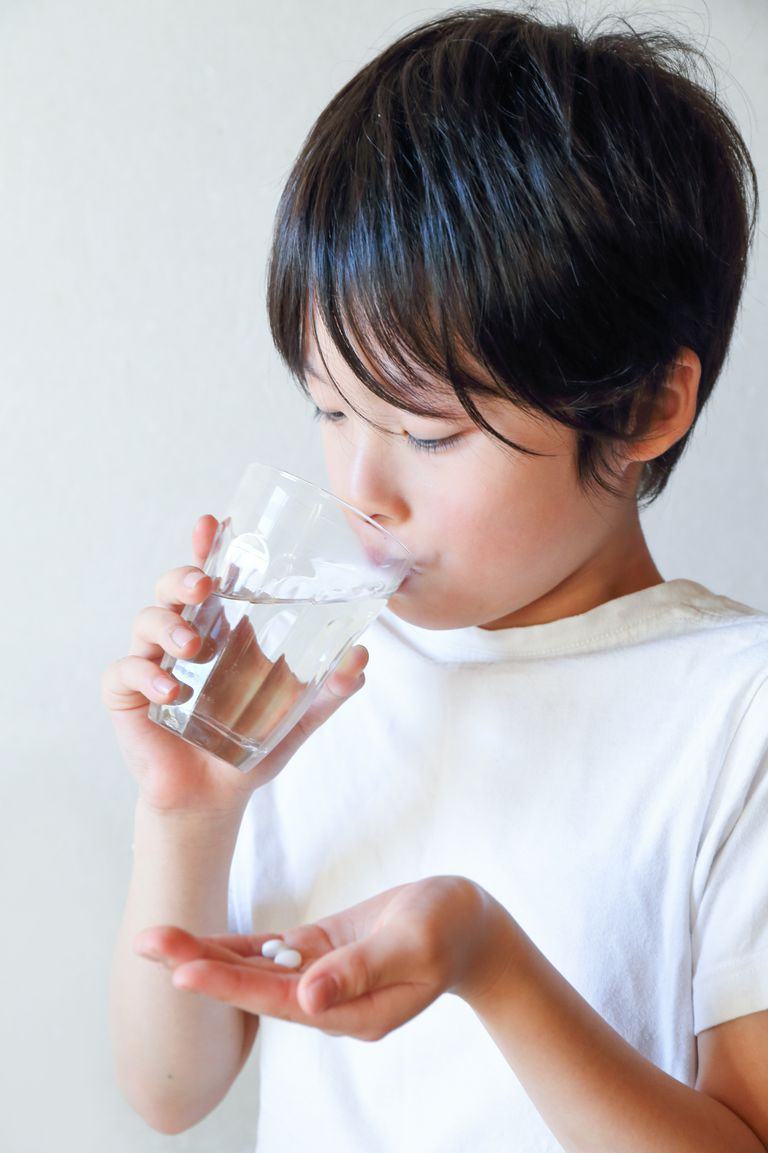 boy taking pills with water