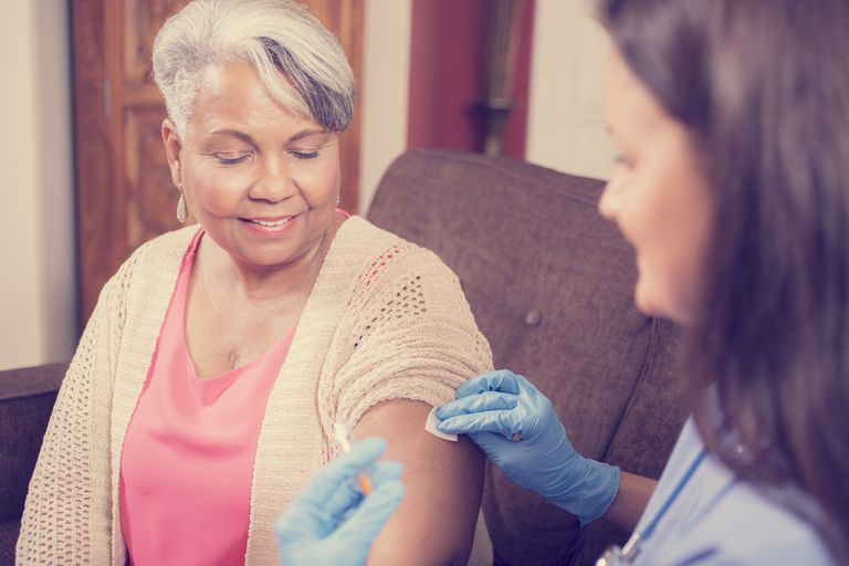 Home healthcare nurse giving injection to senior adult woman.