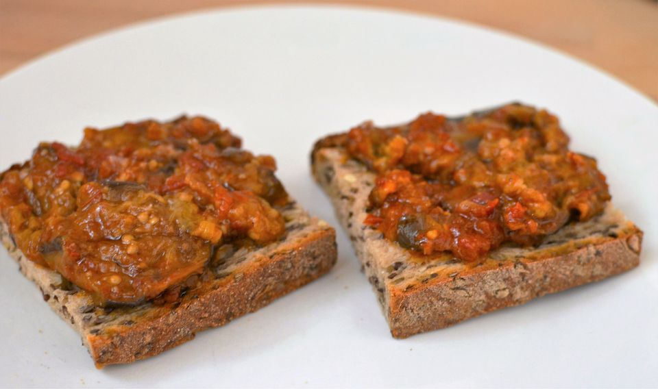 Fried eggplants in tomato sauce, spread on slices of bread