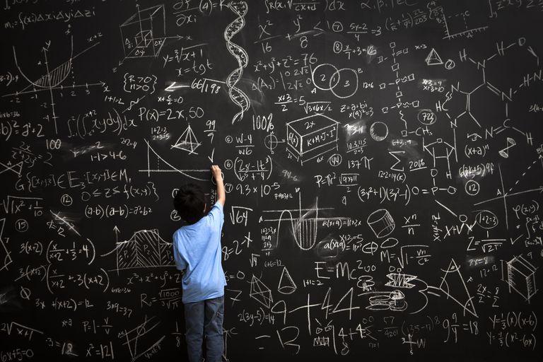 Young boy writes math equations on chalkboard