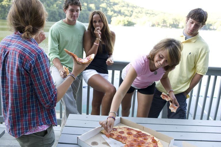Teens eating pizza and hanging out.