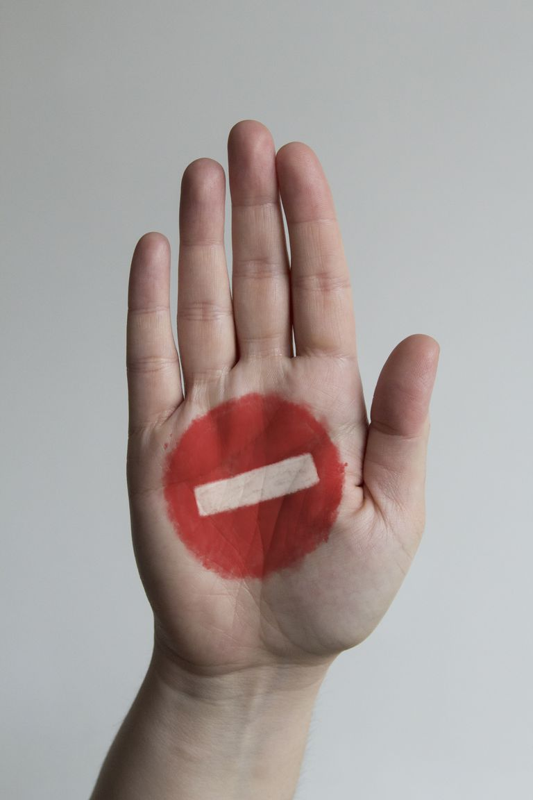 Close-up of stop sign painted on mans hand against gray background