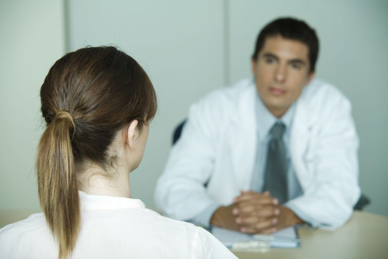 back of woman's head as she is talking to doctor