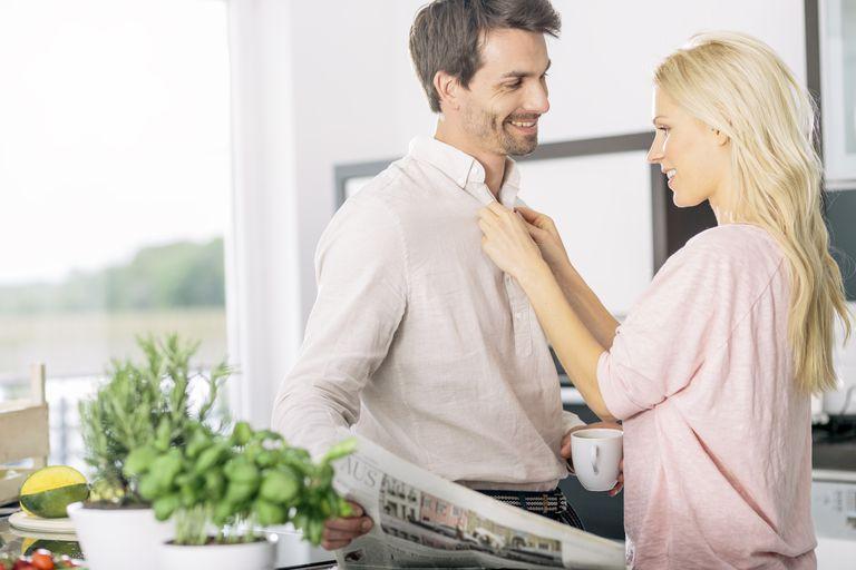 Woman buttoning shirt of her boyfriend