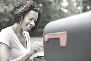 Picture of a woman taking mail from her mailbox