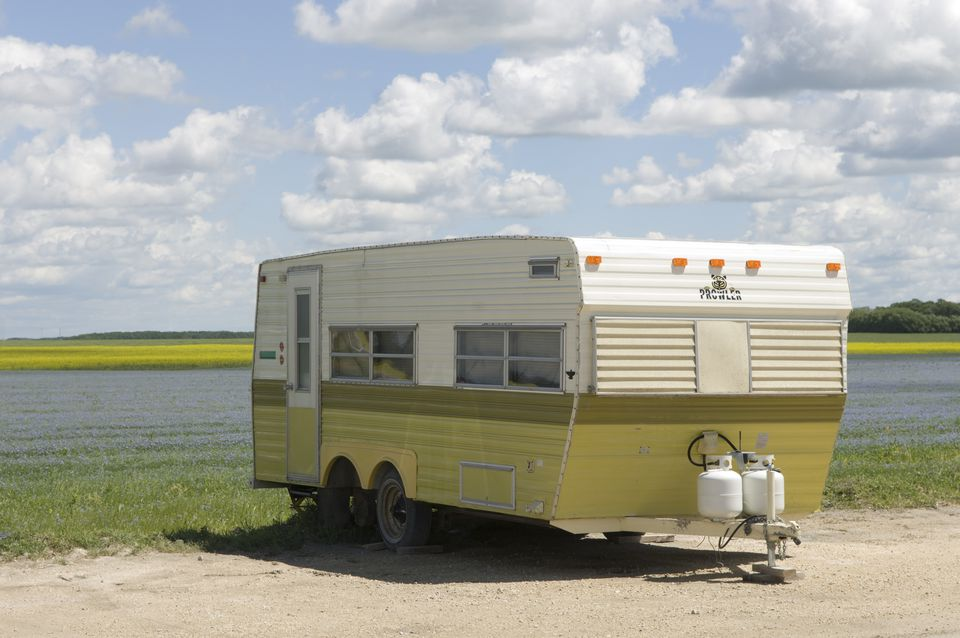 Camper trailer parked at side of alfalfa and canola field near Winnipeg, Manitoba, Canada