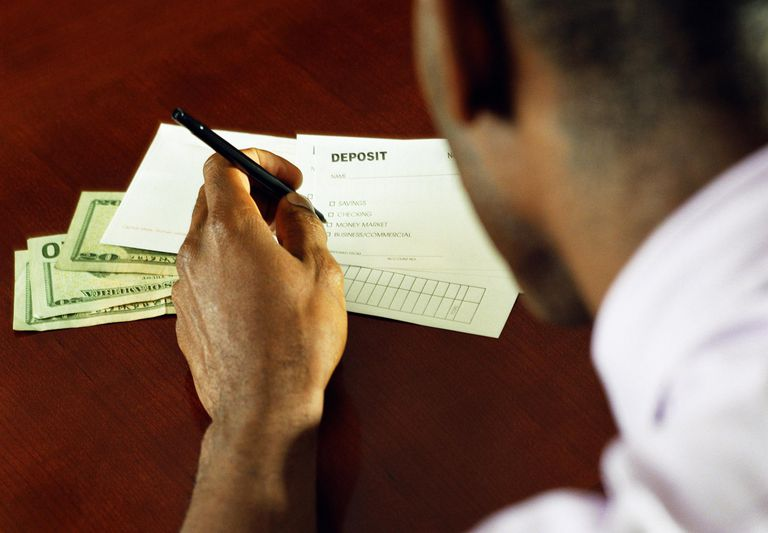 Man filling out bank deposit slip. rear view, close-up (focus on hand)