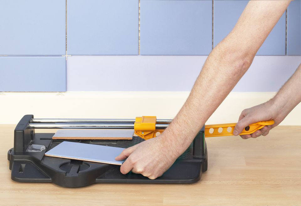 Hand holding cut tile in tile cutter