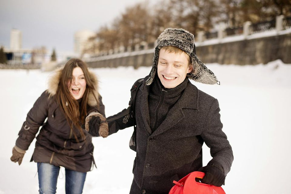 Couple Holding Hands and Laughing In Snow