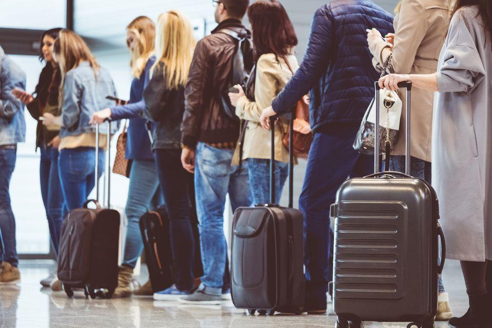 Group of people standing in queue in airport