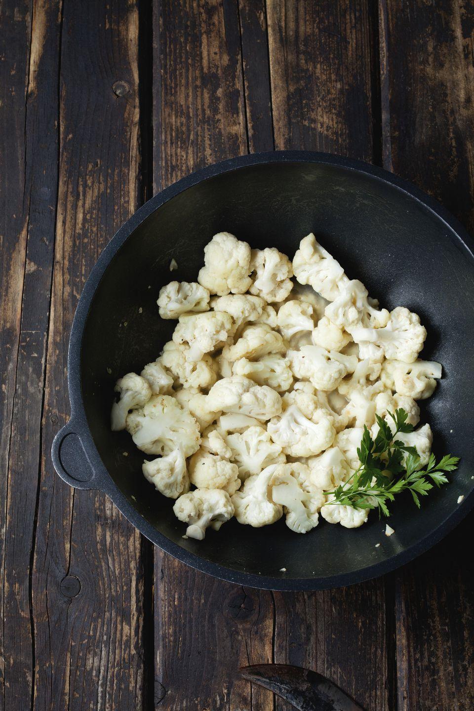 Wok with cauliflower florets on dark wood