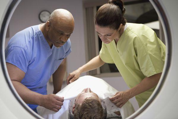 View of technicians preparing patient for MRI, as seen through the MRI machine