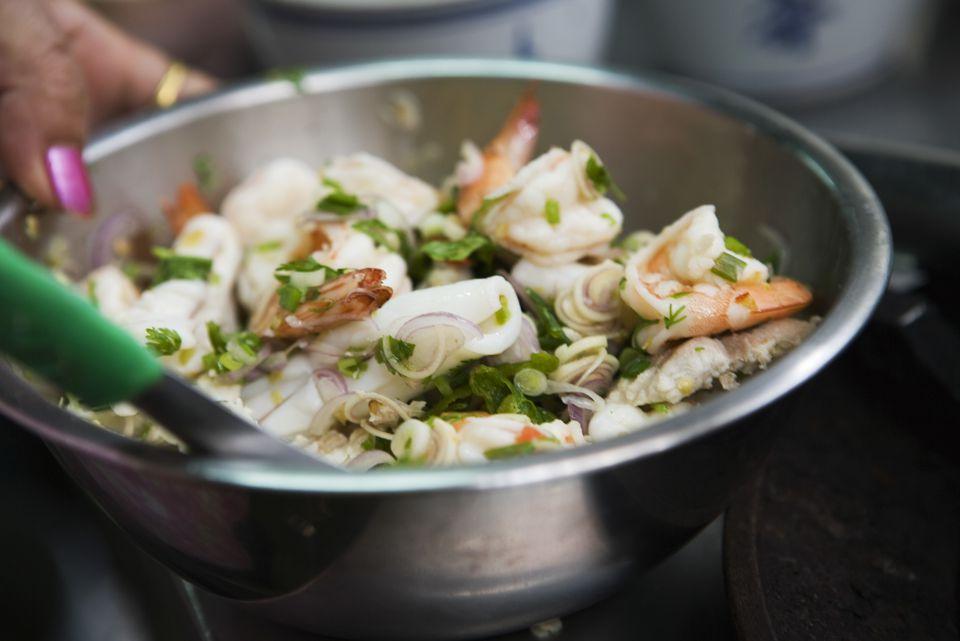 Preparing seafood salad with mint