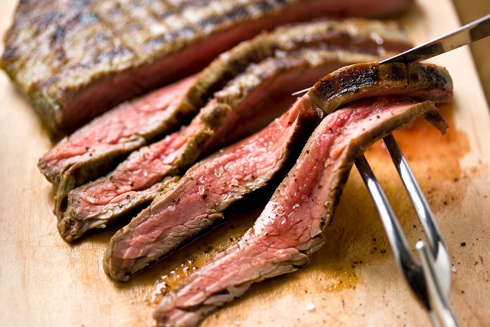 Sliced steak on cutting board with carving utensils, close-up.