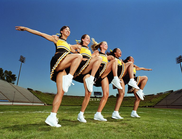 Cheerleaders dancing arm and arm in formation, lifting knee, low angle