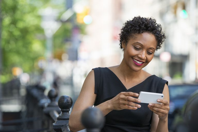 A woman in a black dress on a city street