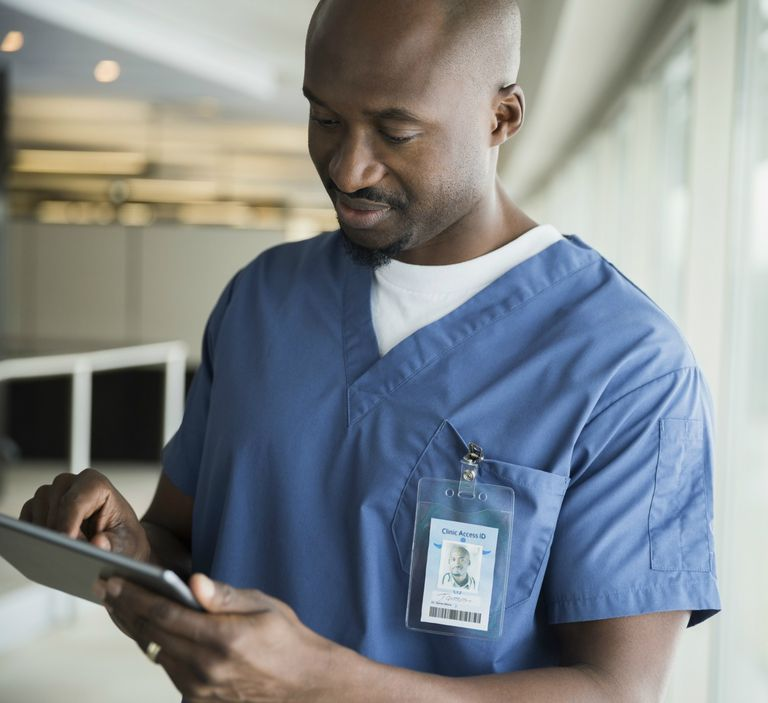 Male nurse using digital tablet at window