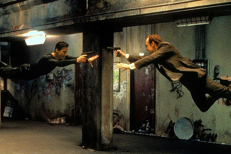Keanu Reeves and Hugo Weaving pointing guns at each other in a scene from the film 'The Matrix', 1999.