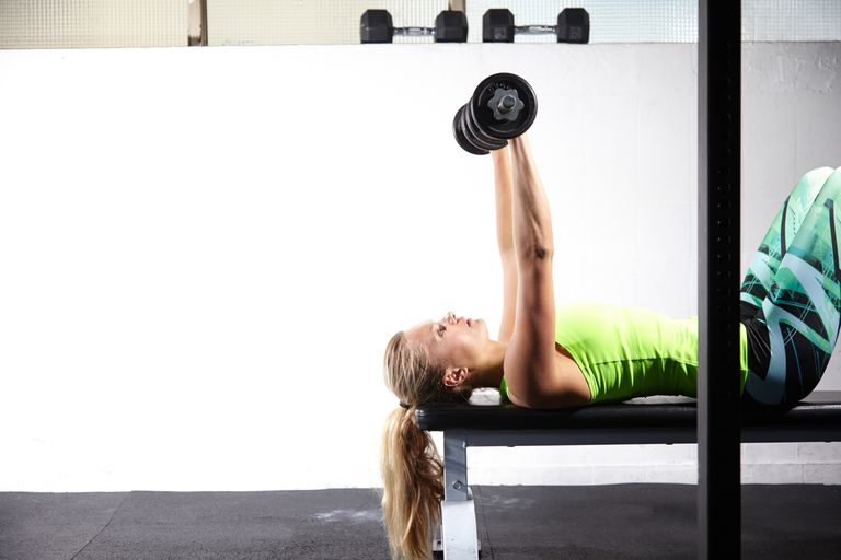 woman doing chest press with dumbbells