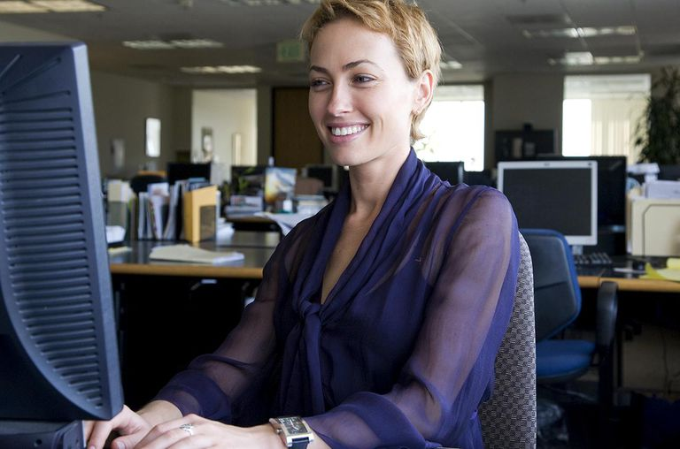 Woman smiling at computer screen in office setting