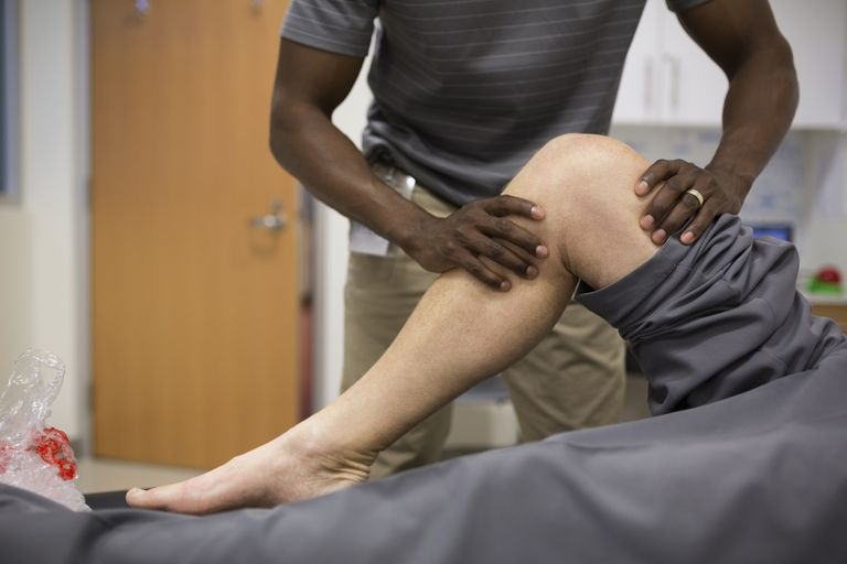 Physical therapist stretching patient's knee