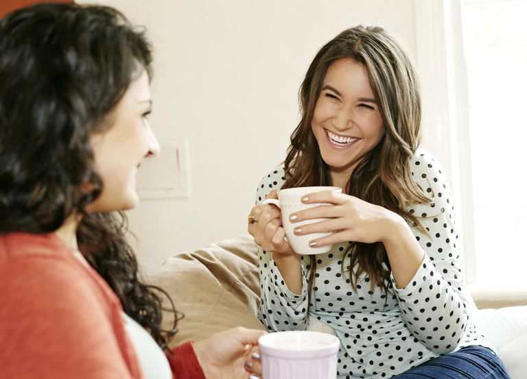 Women having coffee together on sofa