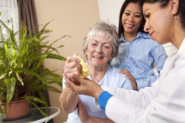 Image of elderly woman receiving hand physical therapy with putty.