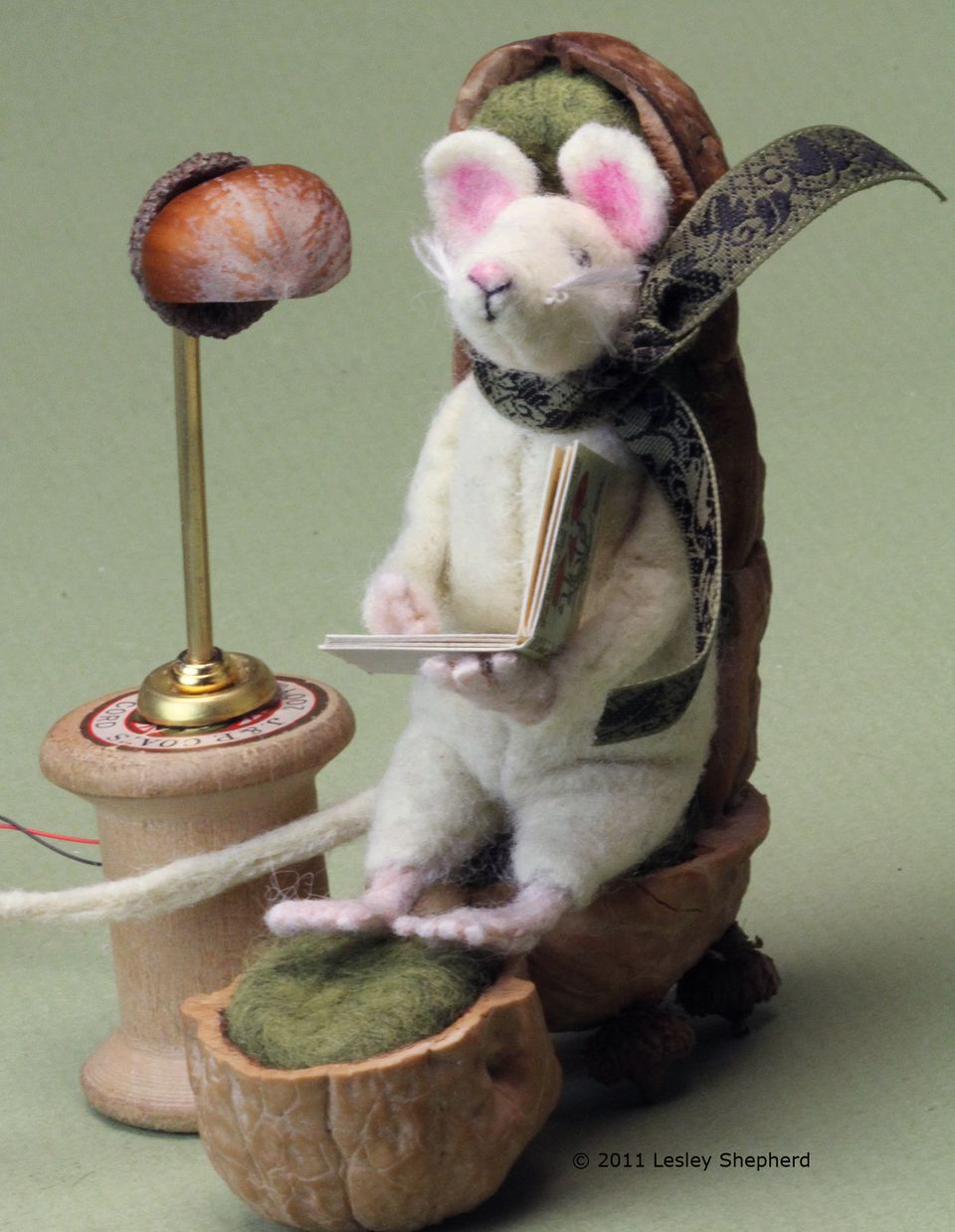 Miniature mouse in his reading chair with a reading lamp on the table beside him.