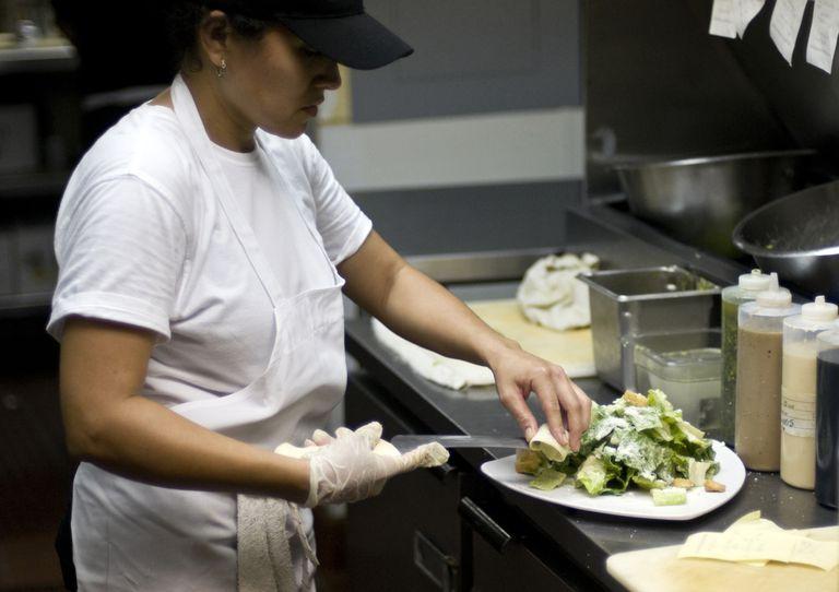 Inmigrante preparando comida en un restaurante.