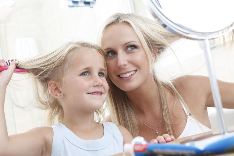 Mother and daughter brushing hair in bathroom