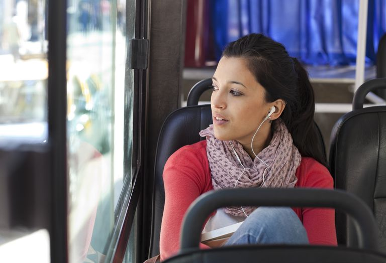 young woman listening to music on a bus
