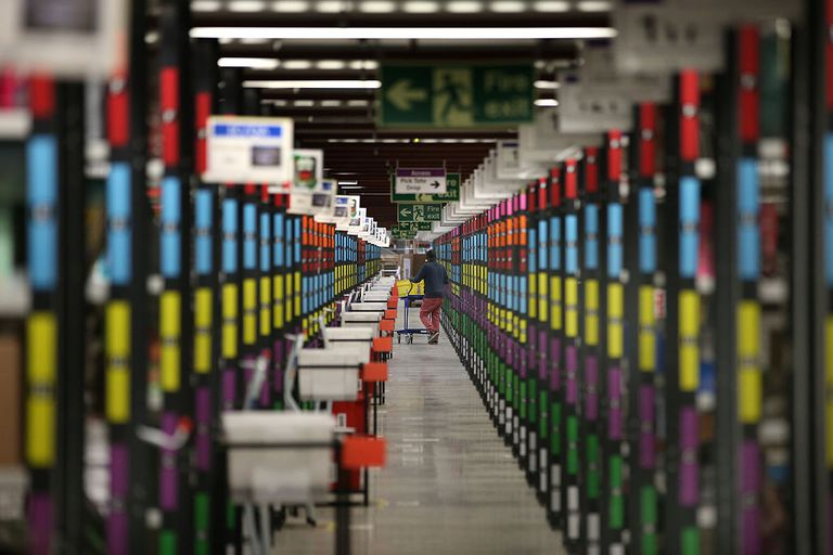 A worker retrieves goods from shelves at Amazon's warehouse