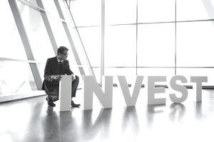 Businessman in suit arranging Invest letters
