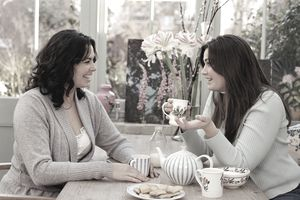 two young women having a conversation over coffee