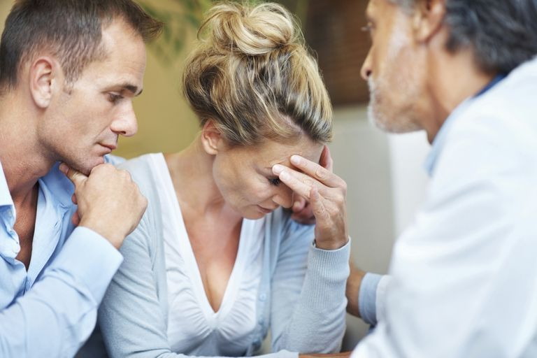 Tensed couple being consoled by doctor