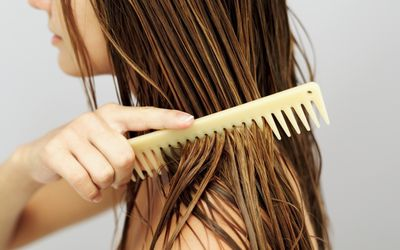 18 flat hair fixes to give fine hair more body woman combing her hair solutioingenieria Images