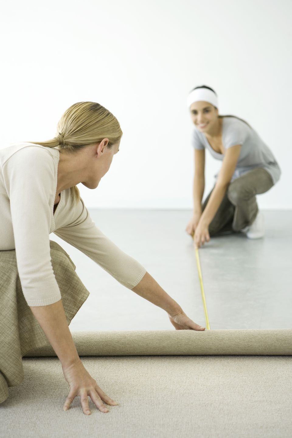 Measuring the floor to calculate how much carpet is required.