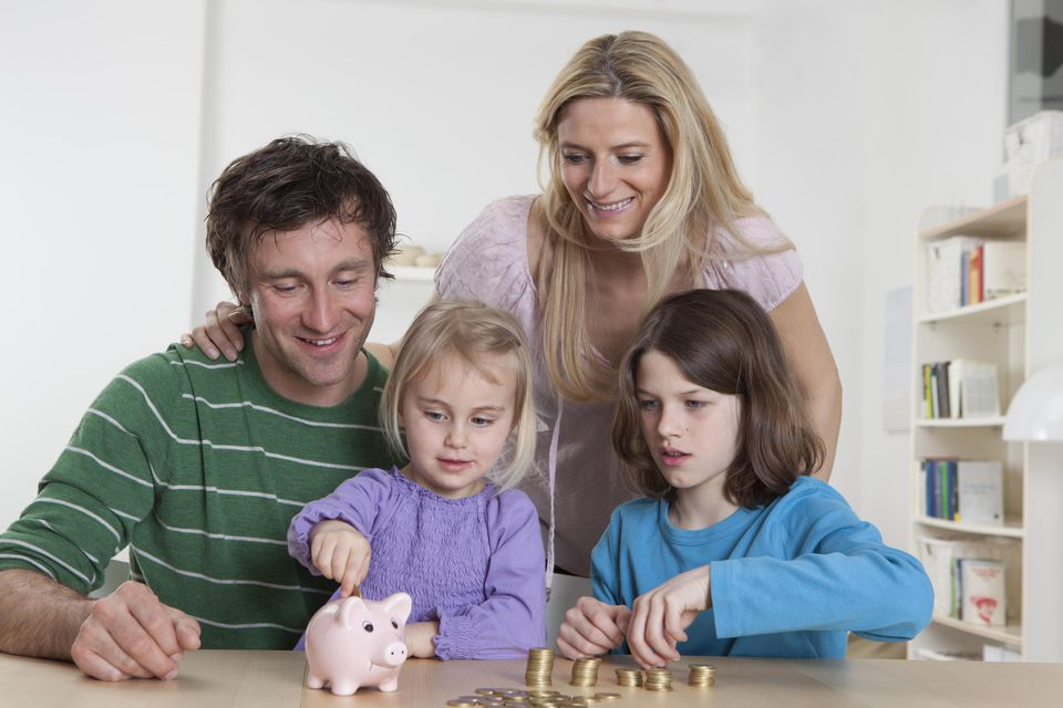 Germany, Bavaria, Munich, Family with coins and piggy bank, smiling