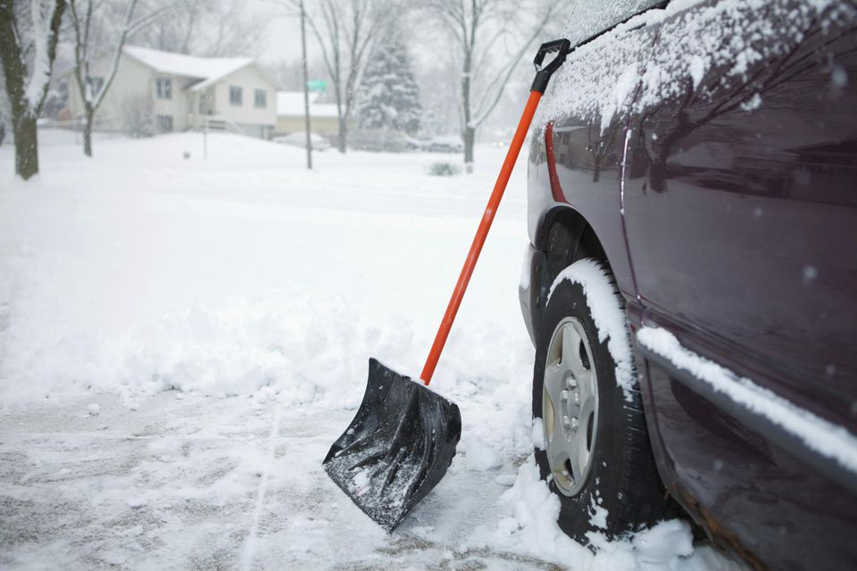 Winter Storm and Snow Shovel leaning against car in Driveway.