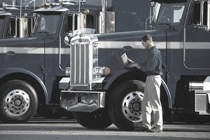 Man with laptop computer standing next to big rigs