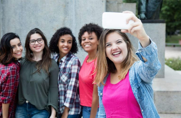 Caucasian woman taking picture of girlfriends with phone
