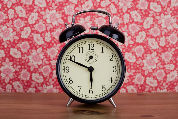 An old fashioned alarm clock in front of floral patterned wallpaper