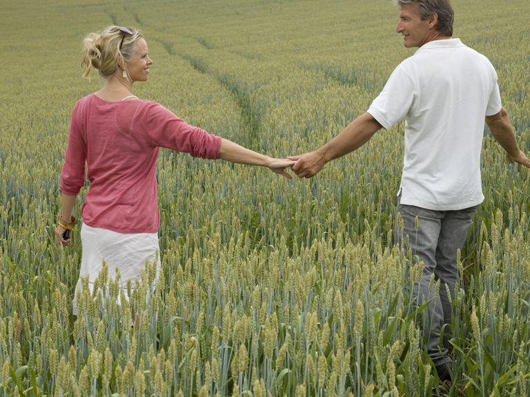 Couple walk hand in hand, field of ripening grain