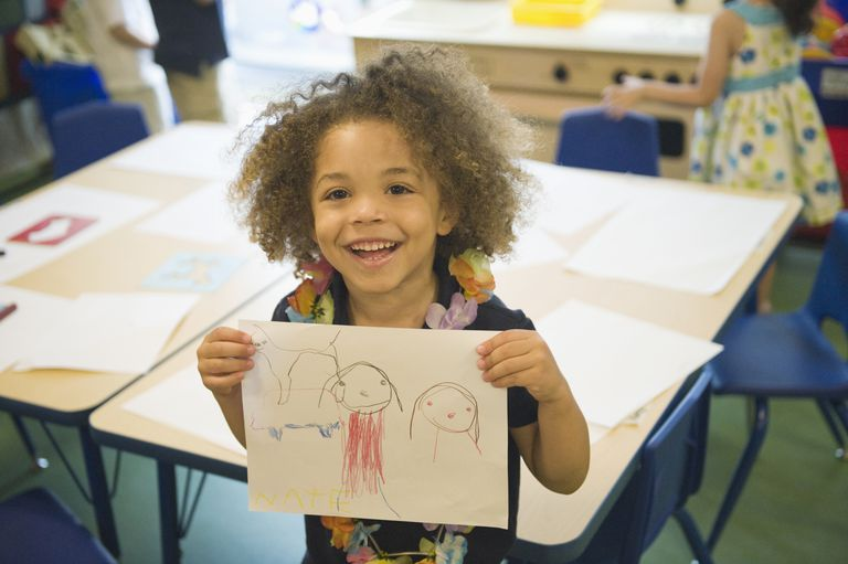 Mixed race boy showing off drawing