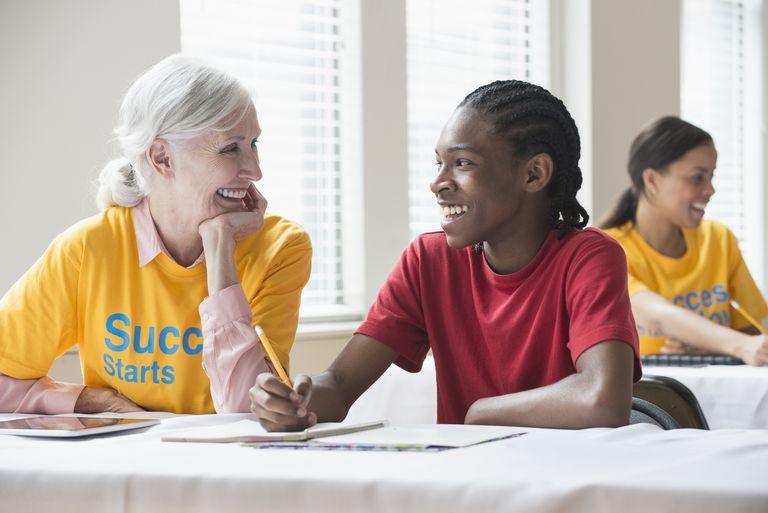 Volunteer helping student in classroom