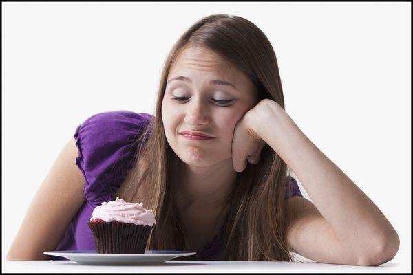 woman resisting cupcake