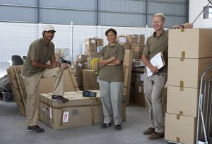 Portrait of three courier employees inside warehouse